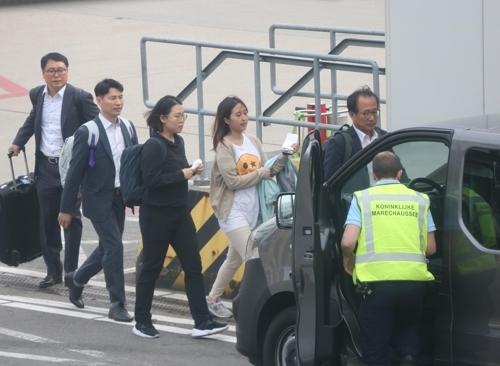 5月30日,在荷兰阿姆斯特丹机场跑道,韩国检方人员护送郑某上车。(韩联社)