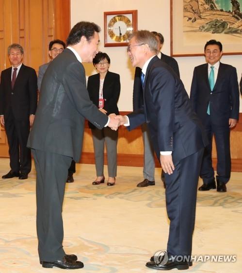 5月31日,在青瓦台,韩国总统文在寅(右)与新总理李洛渊握手。(韩联社)