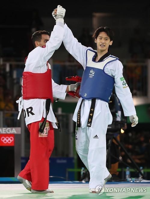 资料图片:里约奥运跆拳道男子68公斤级铜牌得主李大勋(右,韩联社)