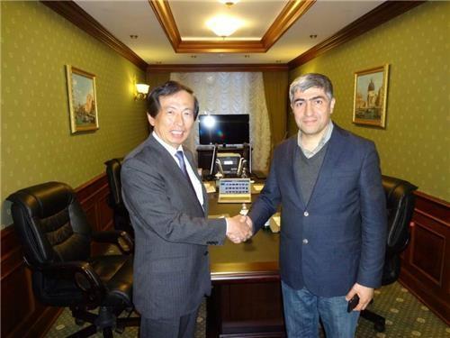 韩联社专务李洪奇(左)与土耳其阿纳多卢通讯社副社长梅廷·穆坦奥卢在签署PNN加入协议后握手合影。(韩联社)
