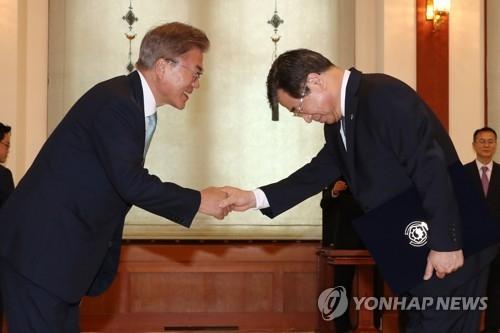 6月1日,在青瓦台,韩国总统文在寅向徐熏(右)颁发国情院长任命书。(韩联社)
