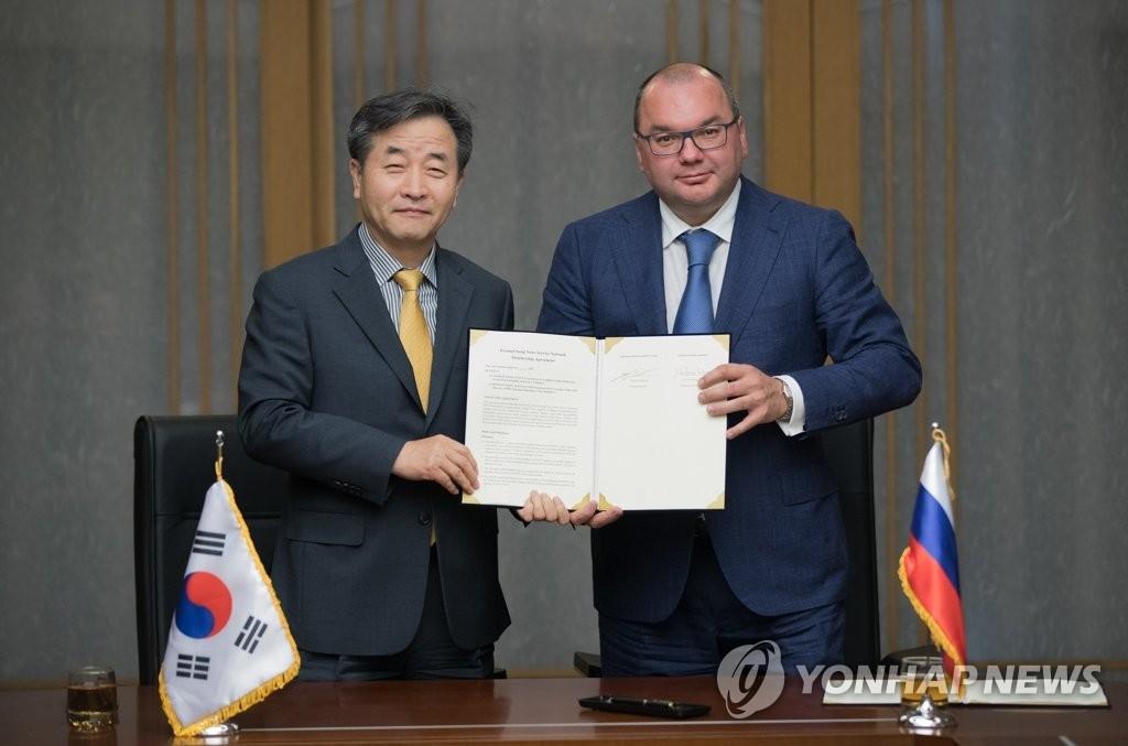 6月5日,在首尔韩联社大楼,韩联社社长朴鲁晃同俄罗斯通讯社塔斯社社长米哈伊洛夫(右)签署PNN加入协议。(韩联社)