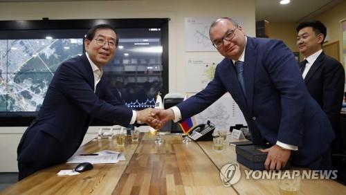 6月5日,在首尔市长接见室,市长朴元淳(左)与米哈伊洛夫握手合影。(韩联社)