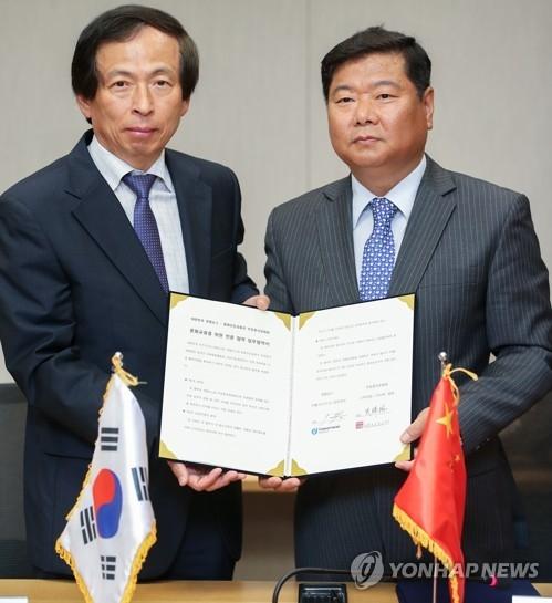 6月7日下午,在首尔市钟路区,韩联社专务李洪奇(左)与中国驻韩文化院长史瑞林在签约后合影。(韩联社)