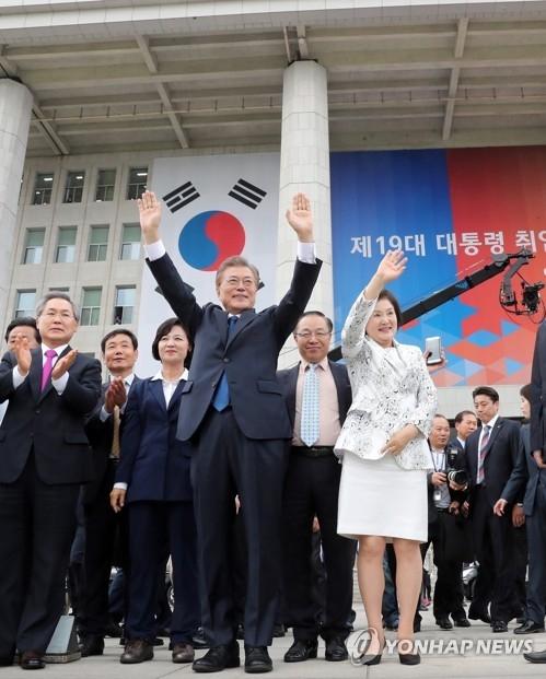 资料图片:5月10日,韩国总统文在寅和第一夫人金正淑在国会出席总统就任仪式后,向现场市民挥手致意。(韩联社)