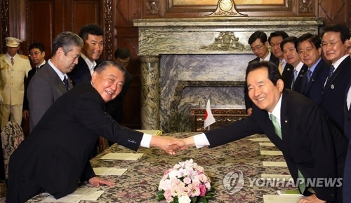 6月8日,在东京,韩国会议长丁世均与日本众议长大岛理森握手。(韩联社/韩国国会发言人室提供)