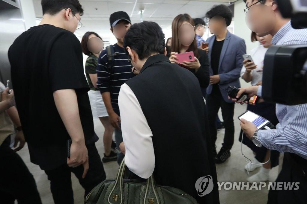 T.O.P的母亲结束探视走出病房。(韩联社)