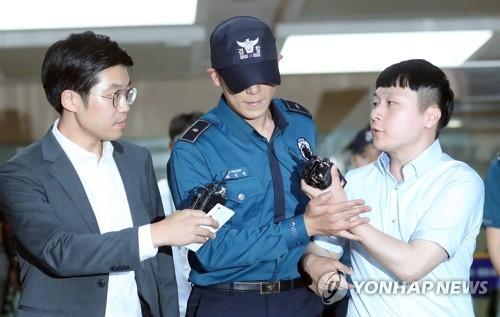 资料图片:BIGBANG成员T.O.P(中)遭记者追问。(韩联社)