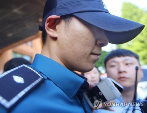 资料图片:6月5日下午,T.O.P离开首尔江南警察署时被记者追问。(韩联社)