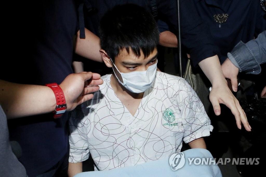 6月9日下午,T.O.P离开首尔梨大木洞医院。(韩联社)