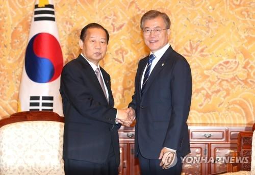 6月12日下午,在青瓦台,韩国总统文在寅接见日本首相安倍晋三的特使、自民党干事长二阶俊博(左)。(韩联社)