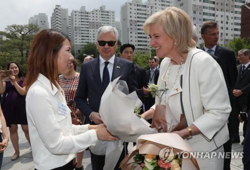 6月13日,在梨花女子大学,学生代表向比利时公主阿斯特丽德(右)献花。(韩联社)