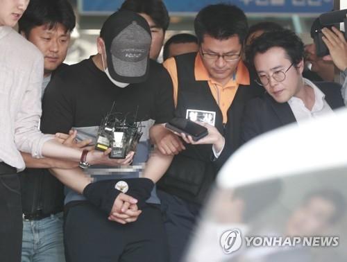 6月15日上午,在首尔市西大门警察署,炸伤导师的学生金某(戴帽子和口罩)前往法院接受羁押必要性审查。(韩联社)