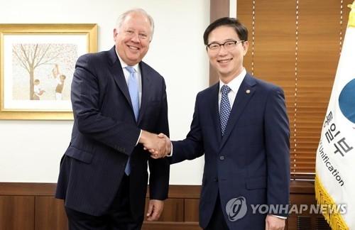 6月15日,在首尔中央政府办公楼,韩国统一部次官(副部长)千海成(右)与到访的美国国务院副国务卿托马斯·香农亲切握手。(韩联社/韩国统一部提供)