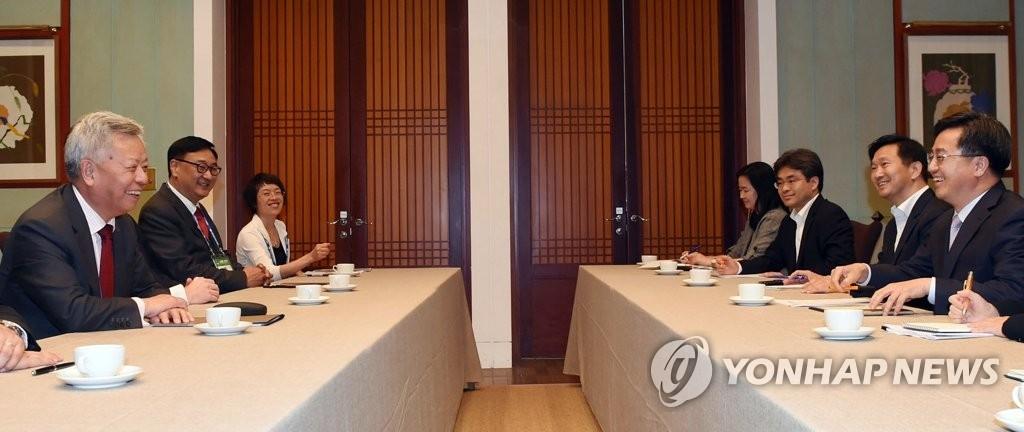 6月15日,在济州新罗酒店,韩国副总理、企划财政部长官金东兗(右)与亚投行行长金立群会面。 (韩联社)