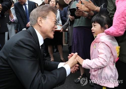 资料图片:文在寅(左)放低身段问候一位韩国儿童。(韩联社)