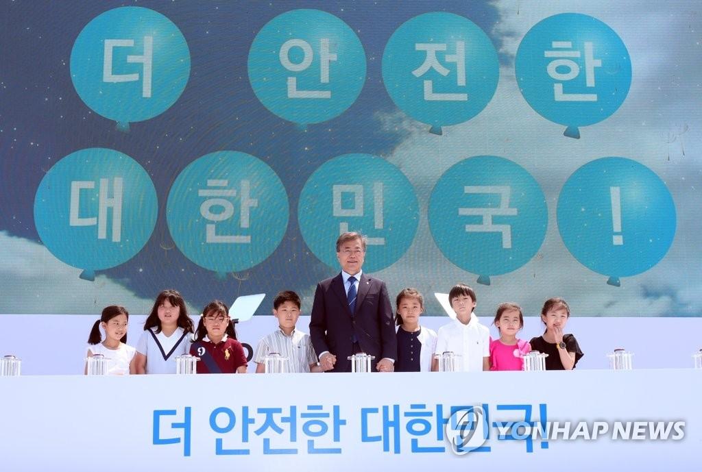 6月19日,文在寅出席古里核电站1号机组永久关闭宣布仪式,并在活动上和小朋友合影。(韩联社)