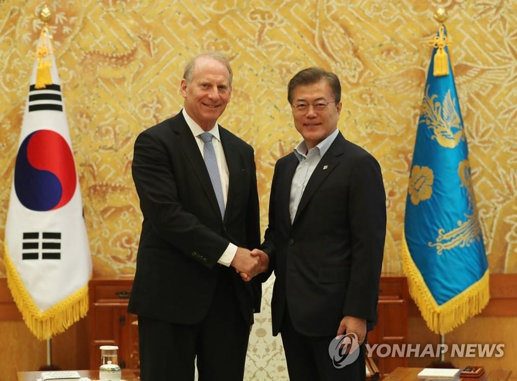 6月21日,在总统府青瓦台,韩国总统文在寅(右)与美国外交学会会长理查德·哈斯握手合影。(韩联社)