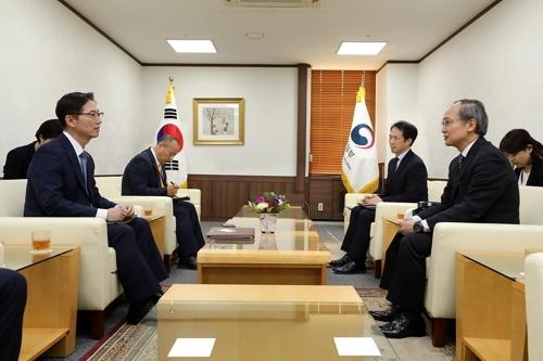 6月21日,在韩国中央政府首尔办公楼,统一部次官千海成(左)与日本驻韩大使长岭安政交谈。(韩联社)