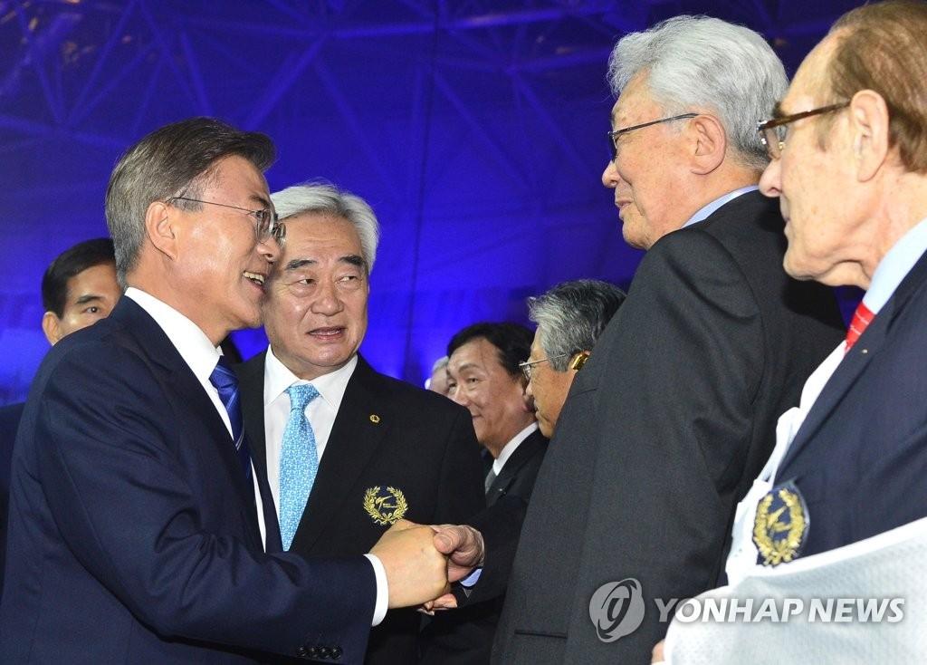 6月24日,在跆拳道世锦赛上,文在寅(左一)和国际奥委会委员张雄握手。(韩联社)