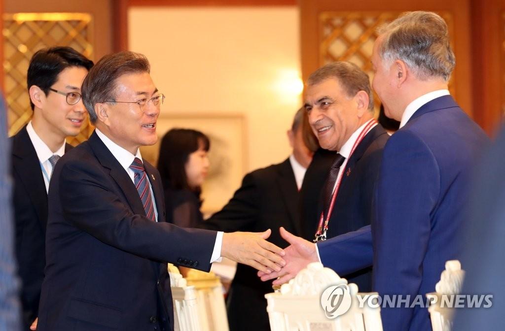 6月27日,韩国总统文在寅出席欧亚国家议长会议午宴,与各国代表亲切握手。(韩联社)