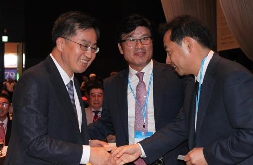 6月28日,在大田ICC酒店,韩国副总理兼企划财政部长官金东兗(左)出席韩中企业家合作展望论坛并和有关人士亲切握手。