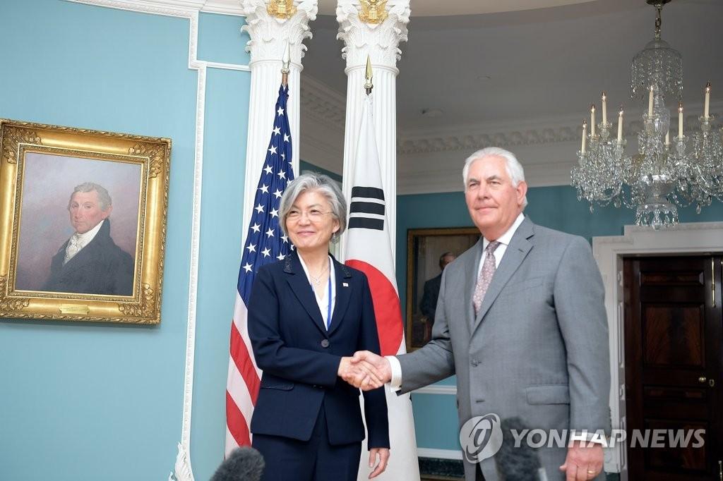 当地时间6月28日,在华盛顿美国国务院大楼,韩国外交部长官康京和(左)与美国国务卿蒂勒森握手。(韩联社/韩国外交部提供)
