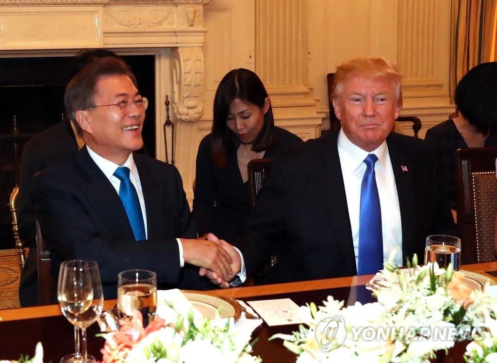 当地时间6月29日,在美国白宫,就职后首次访美的韩国总统文在寅(左)与美国总统特朗普在晚宴开始前握手合影。(韩联社)