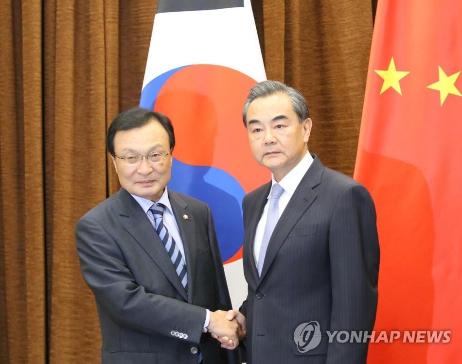 资料图片:5月18日,在北京中国外交部大楼,韩国总统特使李海瓒(左)与中国外交部长王毅握手。(韩联社/北京联合记者团)