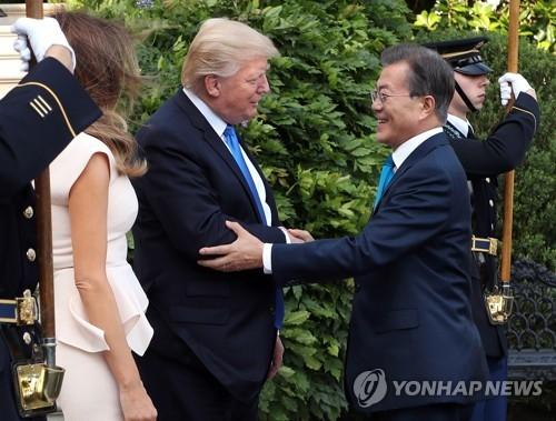 当地时间6月29日,在白宫,文在寅(右二)抵达后与在门口等候的美国总统特朗普(左三)热情握手。(韩联社)