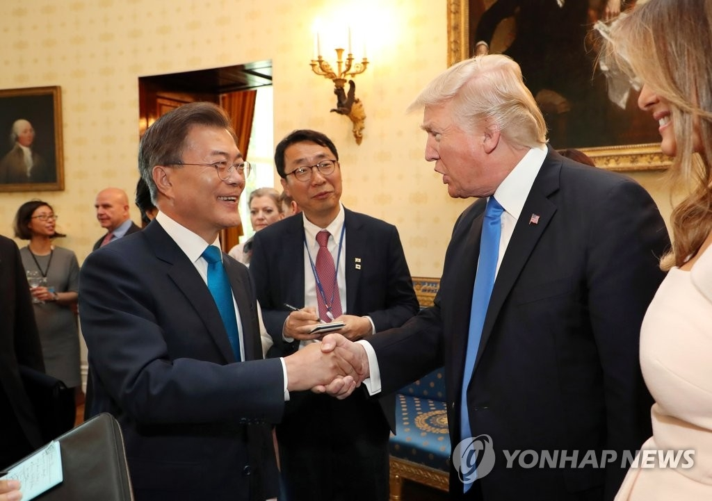 当地时间6月29日,在白宫,文在寅(左)与美国总统特朗普(右二)握手。(韩联社)