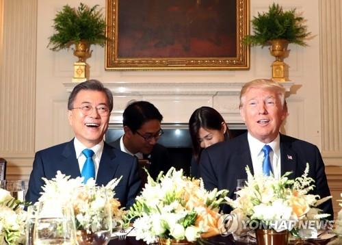 资料图片:当地时间6月29日,在美国白宫,文在寅(左)和特朗普在晚宴上亲切对话。(韩联社)
