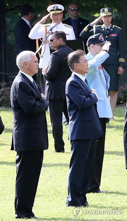 当地时间6月30日上午,在华盛顿国家广场,文在寅和彭斯在向韩战纪念碑献花后对韩美国旗敬礼。(韩联社)
