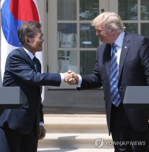当地时间6月30日上午,在白宫,文在寅(左)和特朗普在会谈后的联合记者会上握手。(韩联社)