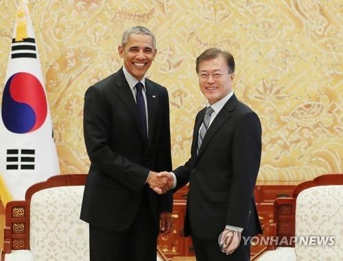 7月3日下午,在青瓦台,文在寅(右)与来访的奥巴马握手。(韩联社/青瓦台提供)