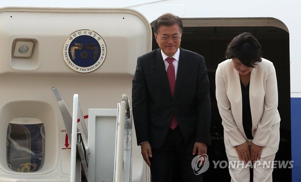 7月5日上午,韩国总统文在寅(左)携夫人金正淑在首尔机场搭乘专机前往德国,在进入机舱前鞠躬致意。(韩联社)