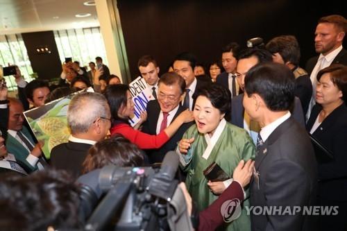 当地时间7月5日,在柏林凯悦酒店,旅德韩人韩侨热烈欢迎文在寅伉俪。(韩联社)