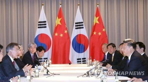 当地时间7月6日上午,在德国柏林一酒店,韩国总统文在寅(左一)和中国国家主席习近平(右一)举行会谈。(韩联社)