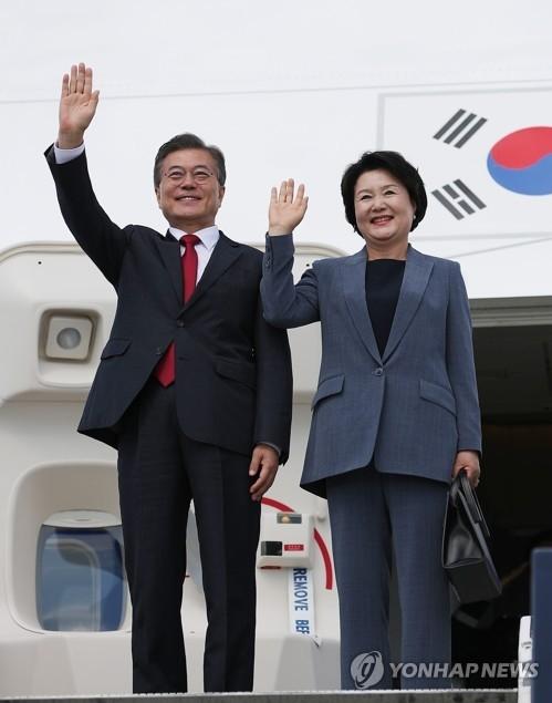 当地时间7月6日下午,韩国总统文在寅和夫人金正淑抵达汉堡,图为两人走出机舱后挥手致意。文在寅将出席在汉堡举行的二十国领导人(G20)峰会。(韩联社)