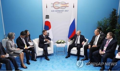 当地时间7月7日,在德国汉堡国际会展中心,韩国总统文在寅(左四)与俄罗斯总统普京(右三)举行会谈。(韩联社)