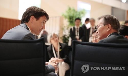 当地时间7月8日,在德国汉堡国际会展中心,韩国总统文在寅(左)会晤加拿大总理特鲁多。(韩联社)