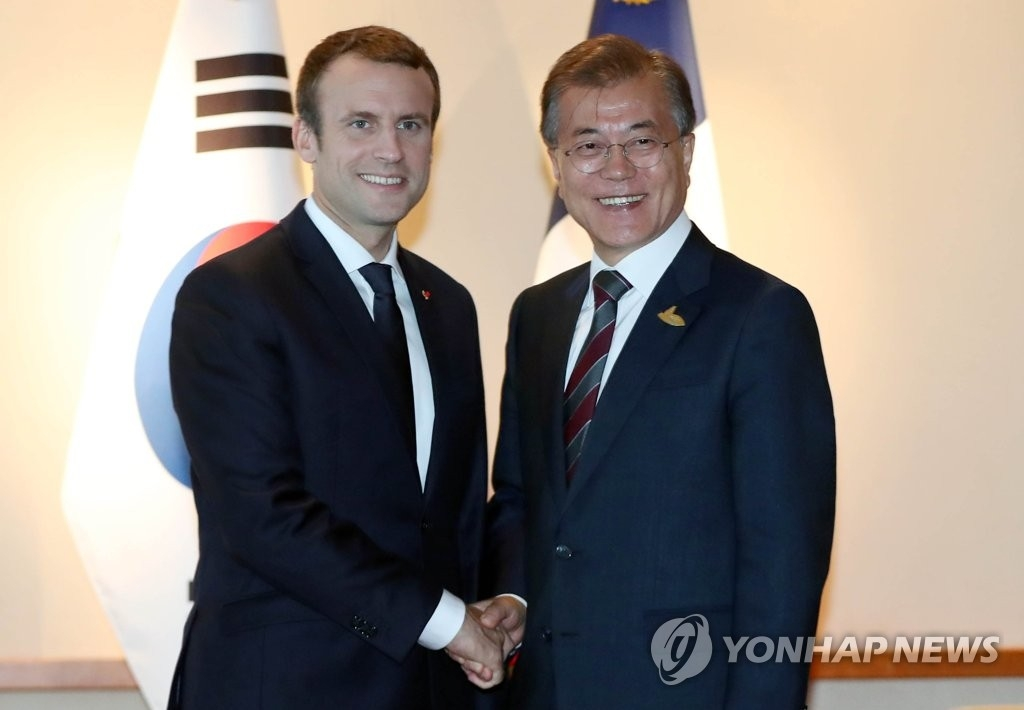 当地时间7月8日下午,韩国总统文在寅(左)与法国总统马克龙在德国汉堡会面,两人握手。(韩联社)