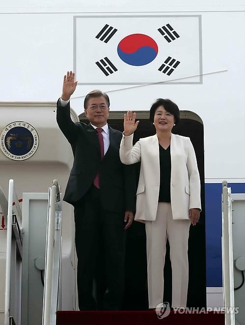 7月5日上午,在首尔机场,韩国总统文在寅(左)和夫人金正淑女士登机前挥手致意。(韩联社)