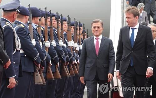 当地时间5日上午,在柏林泰格尔机场,韩国总统文在寅(左)在德国礼宾官员等的陪同下检阅仪仗队。(韩联社)