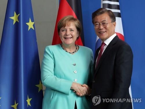 当地时间7月5日,在德国柏林联邦总理府,韩国总统文在寅(右)和德国总理默克尔在联合记者会结束后合影留念。(韩联社)