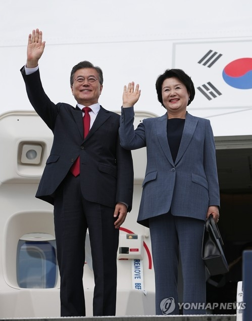 资料图片:当地时间7月6日下午,在德国汉堡,韩国总统文在寅(左)和夫人金正淑女士走出机舱向到机场迎接的人群挥手致意。(韩联社)