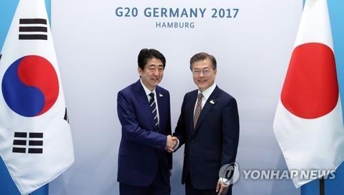 7月7日(当地时间),在德国汉堡,韩国总统文在寅(左)与日本首相安倍晋三在会谈前握手合影。(韩联社)