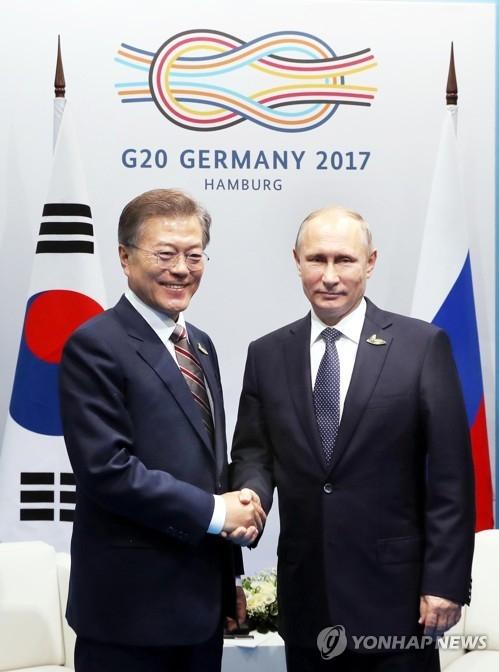 当地时间7月7日下午,在德国汉堡国际会展中心,韩国总统文在寅(左)与俄罗斯总统普京举行会谈。图为双方握手合影。(韩联社)