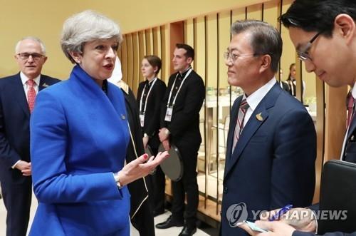 当地时间7月7日下午,在德国汉堡,文在寅在G20峰会领导人合影前与英国首相特蕾莎·梅对话。(韩联社)