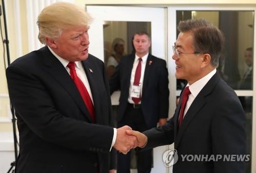 当地时间7月6日下午,在德国汉堡美国总领事馆,韩美日三国首脑即将共进晚餐,图为韩国总统文在寅(右)和美国总统特朗普亲切握手。(韩联社)